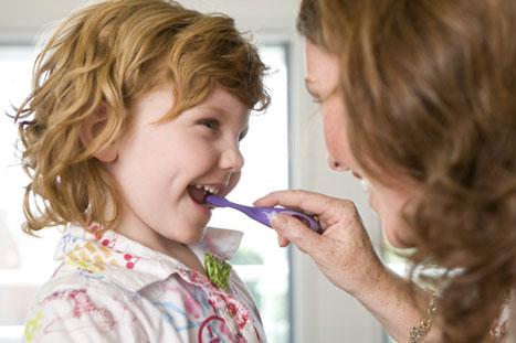 Ibu mengajarkan gosok gigi yang baik.
